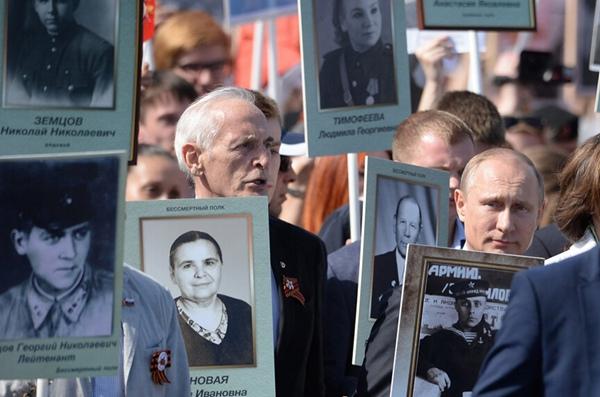 """图为俄罗斯总统普京举父亲肖像参加""""不朽军团""""游行"""