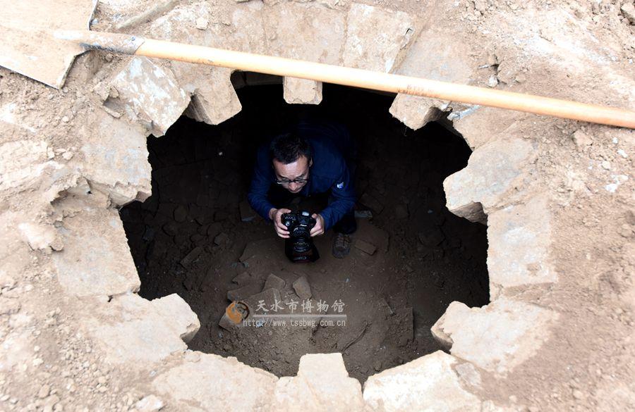 (墓葬清理前)   2017年8月24日,中梁镇机场迁置房建设工地发现一座古代墓葬。经秦州区文化局负责人上报后,天水市博物馆派文物考古研究所专业人员前去勘查并予以清理。由于墓室填满淤土,工程量较大,加上期间又下雨,经过两个星期的清理终于完成。  (墓葬内人骨)   该墓葬位于中梁镇芦家湾南侧约800米处,专业人员起初发现时顶部已被挖开,北侧墓壁被破坏。顶部呈穹隆状,侧面平砖砌成,四角为斜砖。清理完后,发现墓室呈方形,南北向,墓门高大,有台阶甬道。墓室正中放置棺床,以砖砌成须弥座。四壁出现简单的仿木建筑结